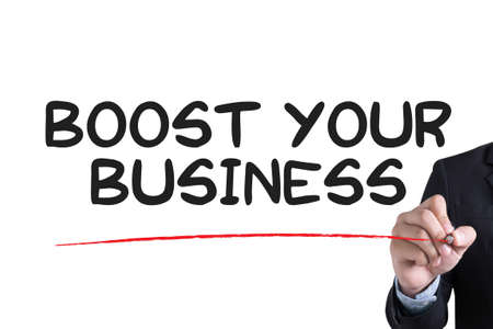 boost: BOOST YOUR BUSINESS Businessman hand writing with black marker on white background