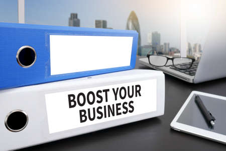 boost: BOOST YOUR BUSINESS Office folder on Desktop on table with Office Supplies.
