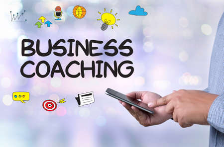 unanswered: BUSINESS COACHING  (Coaching Skills Teach Teaching Training ) person holding a smartphone on blurred cityscape background Stock Photo