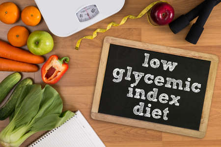 glycemic: low glycemic index diet Fitness and weight loss concept, dumbbells, white scale, fruit and tape measure on a wooden table, top view, free copy space