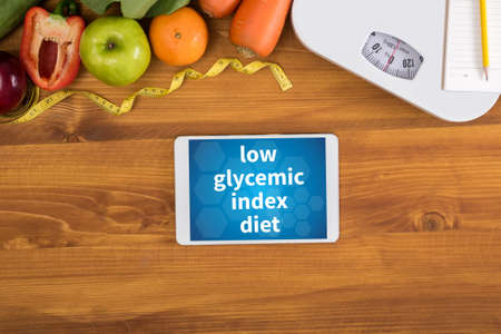 low glycemic index diet top view, digital tablet on a wooden table,  fitness and weight loss concept, dumbbells, white scale, towels, fruit, Weight loss