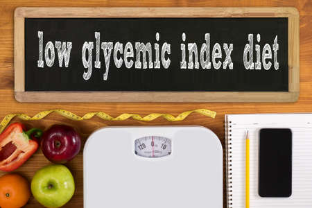 glycemic: low glycemic index diet Fitness and weight loss concept, dumbbells, white scale, fruit and tape measure on a wooden table, top view, free copy space, phone Stock Photo