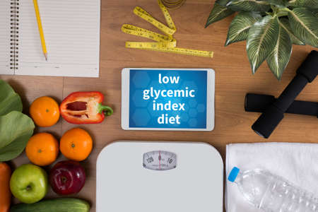 hypoglycaemia: low glycemic index diet top view, digital tablet on a wooden table,  fitness and weight loss concept, dumbbells, white scale, towels, fruit, Weight loss