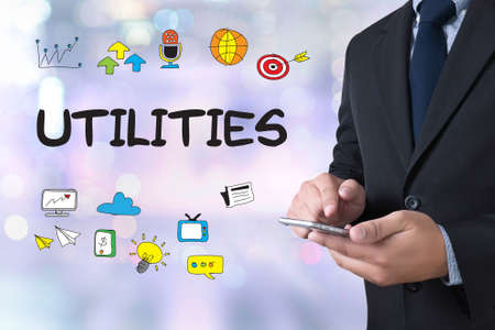 utilities: UTILITIES businessman working use smartphone on blurred abstract background Stock Photo