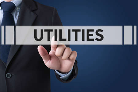 utilities: UTILITIES Businessman hands touching on virtual screen and blurred city background