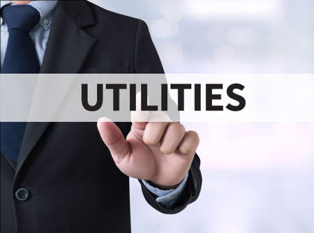 utilities: UTILITIES Businessman touching a touch screen on blurred city background