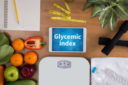 Glycemic index top view, digital tablet on a wooden table,  fitness and weight loss concept, dumbbells, white scale, towels, fruit, Weight loss
