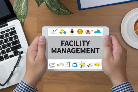 the facility: FACILITY MANAGEMENT man hand Tablet and coffee cup