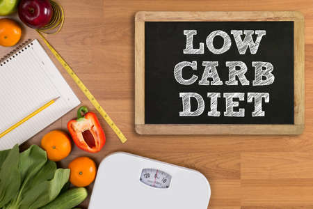 low carb diet: LOW CARB DIET Fitness and weight loss concept, dumbbells, white scale, fruit and tape measure on a wooden table, top view, free copy space Stock Photo