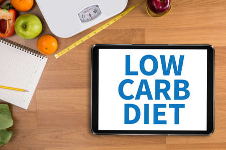 carb: LOW CARB DIET Fitness and weight loss concept, dumbbells, white scale, fruit and tape measure on a wooden table, top view, free copy space Stock Photo