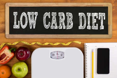 low carb diet: LOW CARB DIET Fitness and weight loss concept, dumbbells, white scale, fruit and tape measure on a wooden table, top view, free copy space, phone