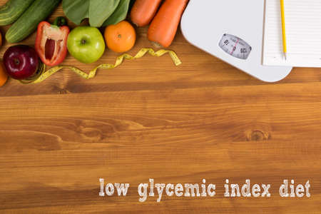 hypoglycaemia: low glycemic index diet Fitness and weight loss concept, dumbbells, white scale, fruit and tape measure on a wooden table, top view, free copy space
