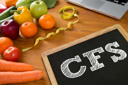 consolidated: CFS  (Consolidated Financial Statement) Fitness and weight loss concept, fruit and tape measure on a wooden table, top view