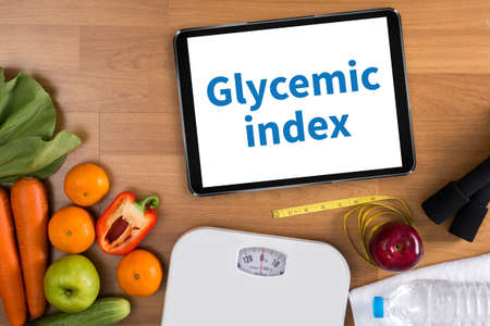 Glycemic index Fitness and weight loss concept, dumbbells, white scale, fruit and tape measure on a wooden table, top view, free copy space Stock Photo