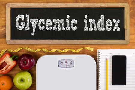 glycemic: Glycemic index Fitness and weight loss concept, dumbbells, white scale, fruit and tape measure on a wooden table, top view, free copy space, phone Stock Photo