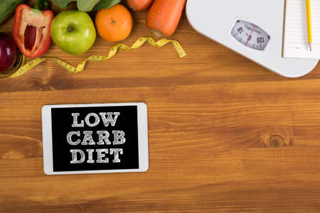 carb: LOW CARB DIET top view, digital tablet on a wooden table,  fitness and weight loss concept, dumbbells, white scale, towels, fruit, Weight loss