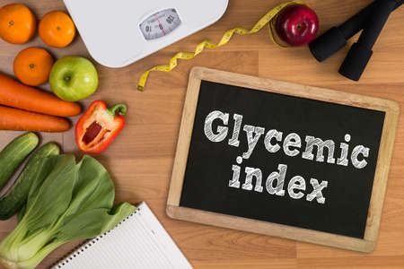 glycemic: Glycemic index Fitness and weight loss concept, dumbbells, white scale, fruit and tape measure on a wooden table, top view, free copy space Stock Photo