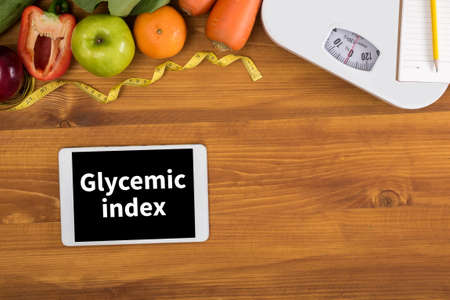hypoglycaemia: Glycemic index top view, digital tablet on a wooden table,  fitness and weight loss concept, dumbbells, white scale, towels, fruit, Weight loss