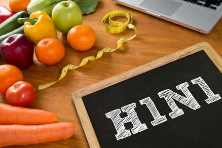 h1n1 vaccination: H1N1 Fitness and weight loss concept, fruit and tape measure on a wooden table, top view