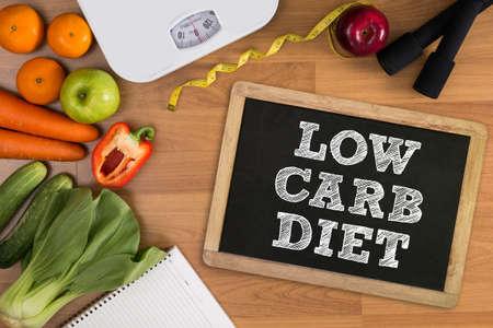 Low Carb dieet Fitness en gewichtsverlies concept, dumbbells, witte schaal, fruit en meetlint op een houten tafel, bovenaanzicht, gratis exemplaar ruimte Stockfoto