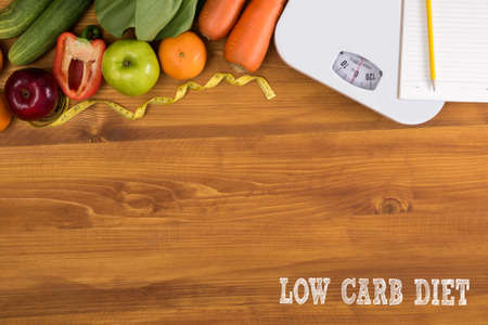 low scale: LOW CARB DIET Fitness and weight loss concept, dumbbells, white scale, fruit and tape measure on a wooden table, top view, free copy space Stock Photo