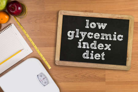 free weight: low glycemic index diet Fitness and weight loss concept, dumbbells, white scale, fruit and tape measure on a wooden table, top view, free copy space