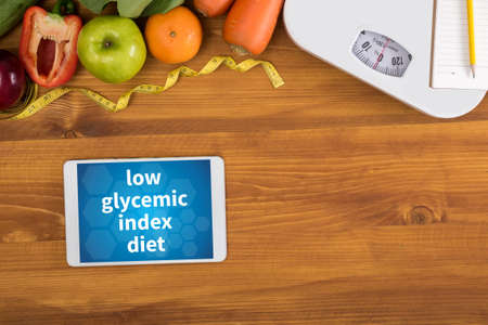 glycemic: low glycemic index diet top view, digital tablet on a wooden table,  fitness and weight loss concept, dumbbells, white scale, towels, fruit, Weight loss