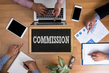 international crisis: COMMISSION Business team hands at work with financial reports and a laptop, top view Stock Photo