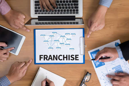 franchising: FRANCHISE    Marketing Branding Retail  Business team hands at work with financial reports and a laptop, top view Stock Photo