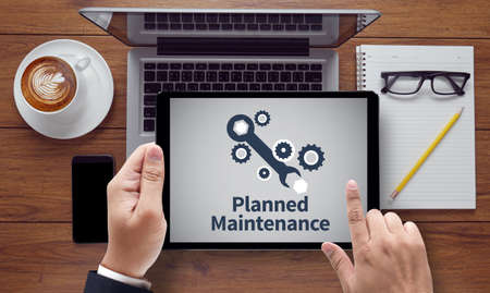 planned: Planned Maintenance, on the tablet pc screen held by businessman hands - online, top view Stock Photo
