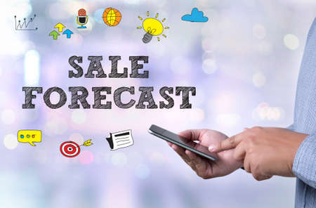 forecasting: SALE FORECAST  ( Forecasting Future Investment) person holding a smartphone on blurred cityscape background Stock Photo