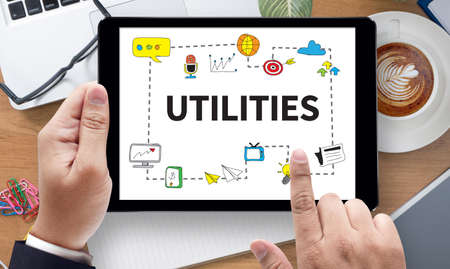 utility payments: UTILITIES, on the tablet pc screen held by businessman hands - online, top view