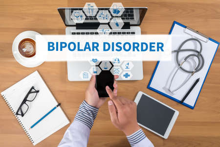 psychosis: BIPOLAR DISORDER Doctor working at office desk and using a mobile touch screen phone, computer and medical equipment all around, top view, coffee Stock Photo