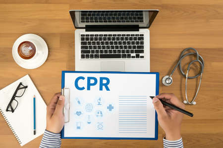 writing equipment: CPR      Cardiopulmonary resuscitation Basic life support ( BLS )and Advanced cardiac life support ( ACLS )( mouth to mouth Doctor writing medical records on a clipboard, medical equipment and desktop on background, top view, coffee
