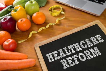 reform: HEALTHCARE REFORM Fitness and weight loss concept, fruit and tape measure on a wooden table, top view Stock Photo