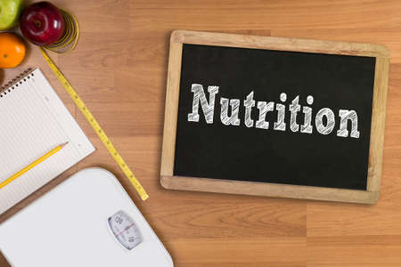what to eat: Nutrition Diet Healthy Life And Eating Fitness and weight loss concept, dumbbells, white scale, fruit and tape measure on a wooden table, top view, free copy space