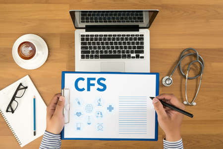 financial statement: CFS  (Consolidated Financial Statement) Doctor writing medical records on a clipboard, medical equipment and desktop on background, top view, coffee