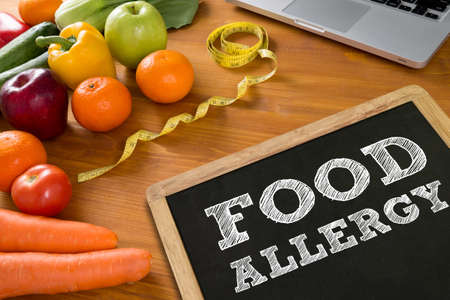 FOOD ALLERGY Fitness and weight loss concept, fruit and tape measure on a wooden table, top view
