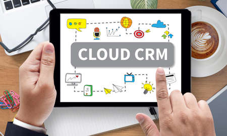 interactions: CLOUD CRM, on the tablet pc screen held by businessman hands - online Hand Touching Cloud CRM, top view Stock Photo