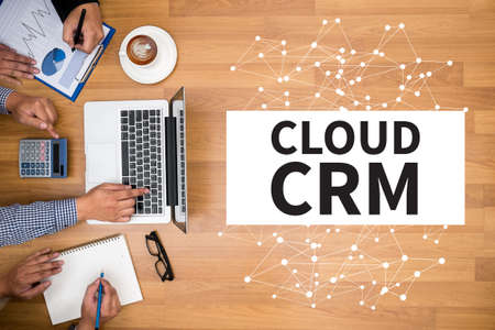 interactions: CLOUD CRM Business team hands at work with financial reports and a laptop