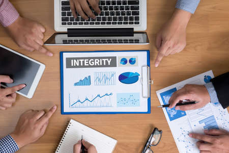 INTEGRITY   Ethics Loyalty Moral Motivation Business team hands at work with financial reports and a laptop, top view Stock Photo