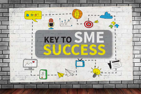 enterprises: KEY TO SME SUCCESS  Small and medium-sized enterprises on brick wall and poster concept Stock Photo
