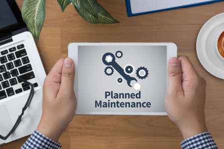 scheduled replacement: Planned Maintenance man hand Tablet and coffee cup Stock Photo