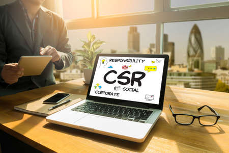 norms: Corporate  Social Responsibility CSR and   Sustainability Responsible Office  CSR Thoughtful male person looking to the digital tablet screen, laptop screen,Silhouette and filter sun Stock Photo