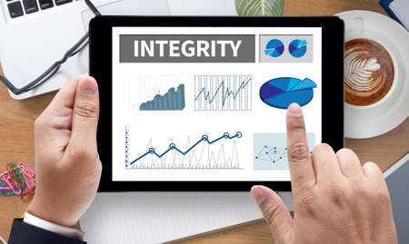 INTEGRITY   Ethics Loyalty Moral Motivation, on the tablet pc screen held by businessman hands - online, top view Stock Photo