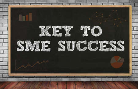 enterprises: KEY TO SME SUCCESS  Small and medium-sized enterprises on brick wall and chalkboard background