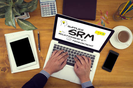 interactions: man work SRM Supplier Relationship Management  Assessment Enterprise Analysis  Close up of business man hand working  laptop computer on wooden desk Stock Photo