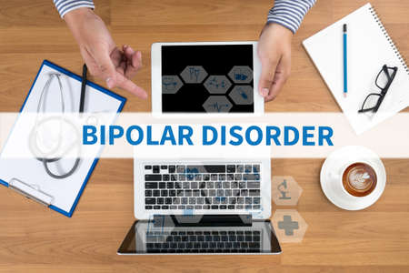 psychosocial: BIPOLAR DISORDER Doctor touch digital tablet, desktop with medical equipment on background, top view, coffee