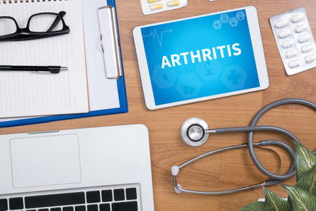 spondylitis: ARTHRITIS Professional doctor use computer and medical equipment all around, desktop top view Stock Photo