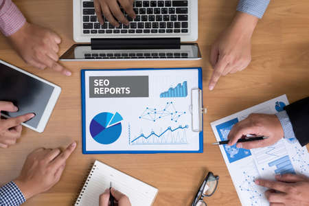 financial reports: SEO REPORTS Business team hands at work with financial reports and a laptop, top view Stock Photo